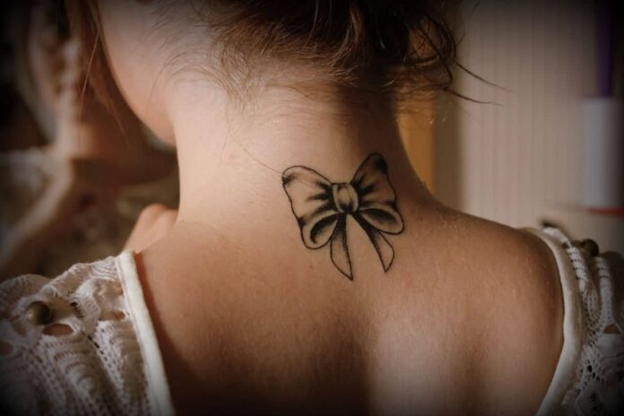 Awesome-Bow-Tattoo-On-Girl-Back-Neck